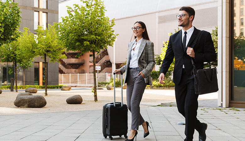 couple wearing suits, glasses and carrying luggage