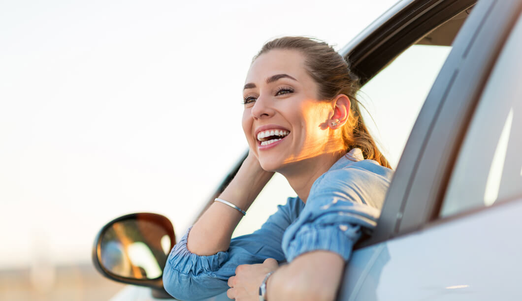smiling girl inside a car